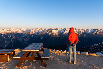 A woman is seeing the scenery of Mount Tsubakuro Dake at sunset. Snow mountain range of Norther Japan Alps Chubu-Sangaku Park.