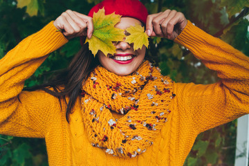 Autumn woman in autumn park. Warm sunny weather. Fall concept.Pretty girl in a beret and a sweater in autumn park