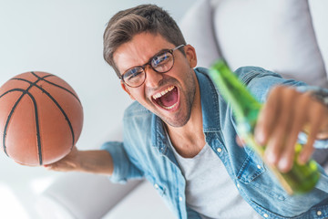 Basketball fan. Cheerful young man watching TV and holding basketball ball while gesturing on the couch at home