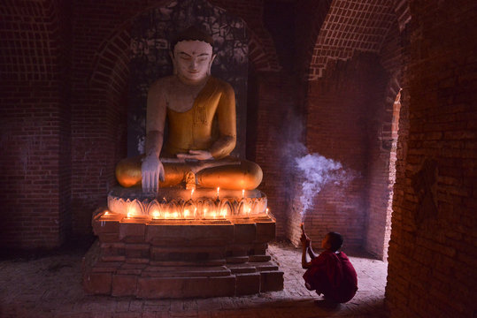 young budhist pilgrim  monk dressed in traditional red robe praying in front of buddha in a temple in myanmar