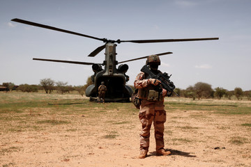 """A French soldier of the the """"Belleface"""" Desert Tactical Group (GTD) secures a Boeing CH-47 Chinook military helicopter of the British army during the Operation Barkhane in Ndaki"""