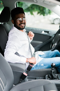 Portrait of handsome young indian man sitting in driving seat of car and wearing seatbelt for safety