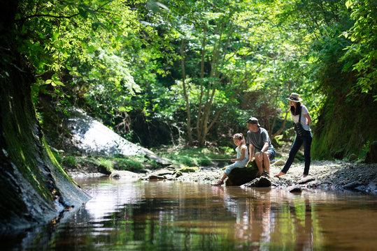 渓流で釣りをする父と母と娘