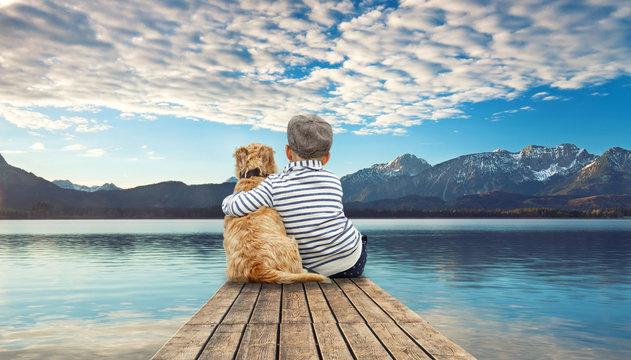 romantischer Steg am Bergsee - kleiner Junge mit Hund
