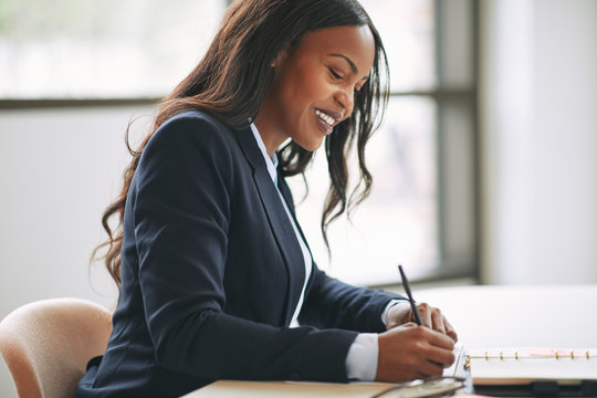 Smiling African American businesswoman writing notes in her day