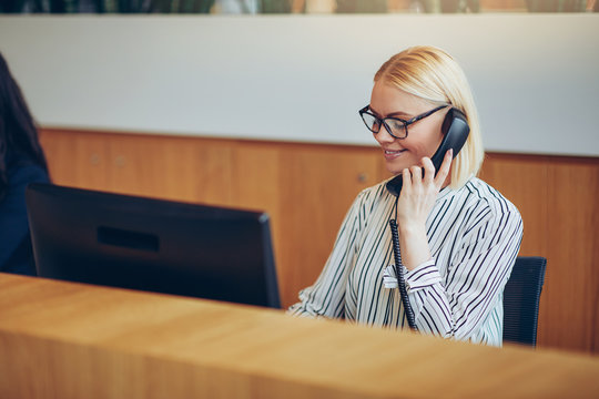 Businesswoman smiling while talking on the telephone in an offic