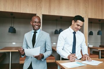 Two smiling diverse businessmen going over paperwork in an offic