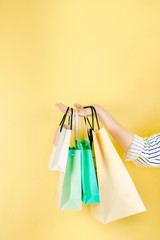 mid season sale and shopping activity from hand hold the shopping bag with copy space and yellow vintage background