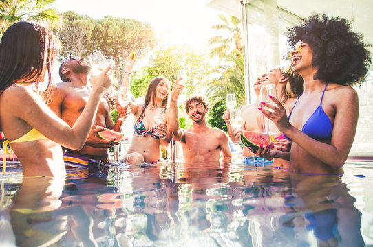 Multi-ethnic group of friends toasting champagne on a pool party