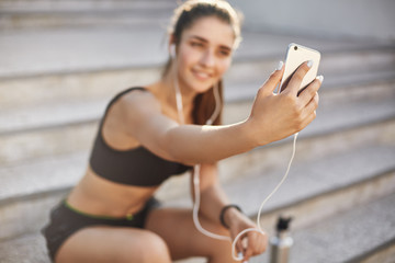 Blurred shot with focus on smartphone, attractive cheerful female athlete sit outdoors staircase,...