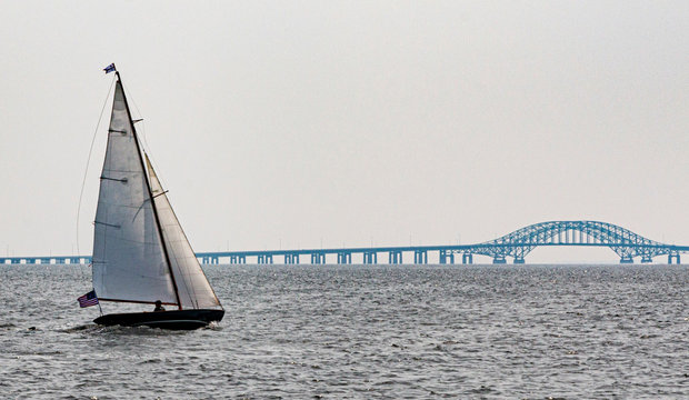 Sailboat sailing toward bridge in the Great South Bay Babylon