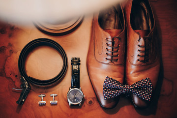 Stylish watch, expensive, shoes, bow tie, cufflinks and belt for groom on wooden table in hotel room. Morning preparation before wedding ceremony. Men accessory for luxury event