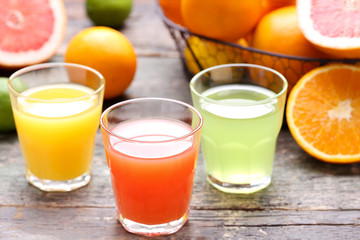 Wall Mural - Citrus juice in glasses with fruits on grey wooden table