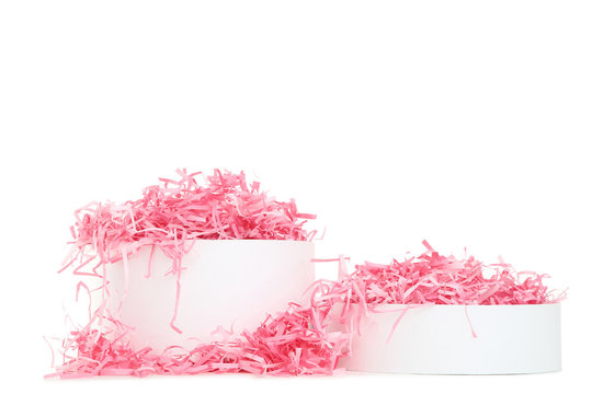 Open gift box with pink shredded paper on white background