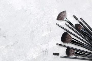 Set of makeup brushes on grey background