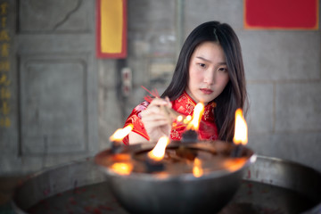 Beautiful Asian girl burning incense upon the incense altar in the Chinese temple.