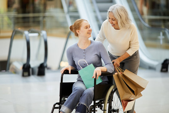 Senior mother with shopping bags laughing and talking to her daughter while carrying her in wheelchair in the shopping centre