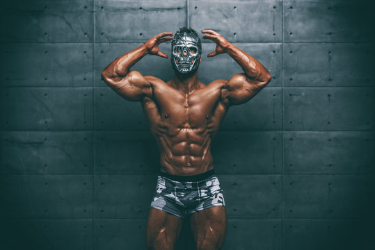 Mysterious Muscular man hiding behind mask Flexing Muscles. Bodybuilder with mask on his face posing.