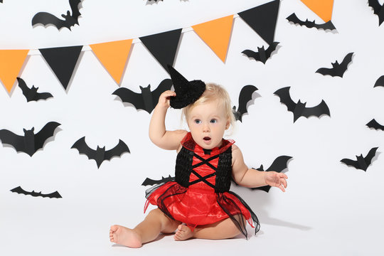 Baby girl in halloween costume on white background