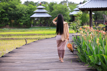 Behind the woman's long hair, wearing a traditional dress, carrying an umbrella, walking in a wooden pathway