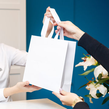 Woman receptionist in white uniform gives a gift packet to a client. Reception in beauty salon, medical center or clinic.