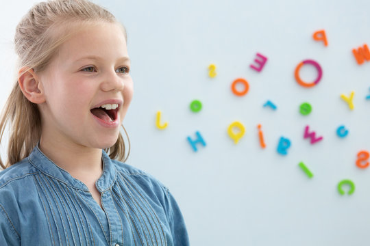 Cute blond little girl opening her mouth during speech therapy, copy space on the wall with letters