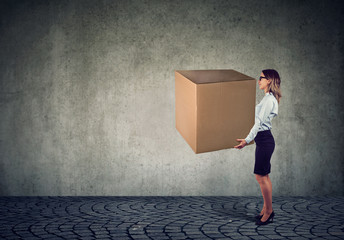 Business woman carrying a huge box