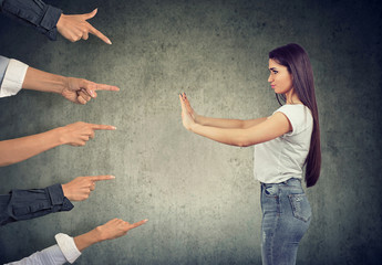 woman defending herself from blaming people with pointing fingers at her