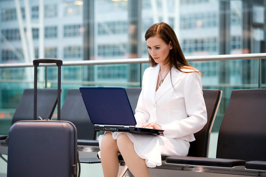 Business woman sitting in airport lounge, using laptop