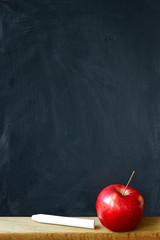 Close-up black chalk board in chalk stains chalk board and red apple, selective focus, copyspace