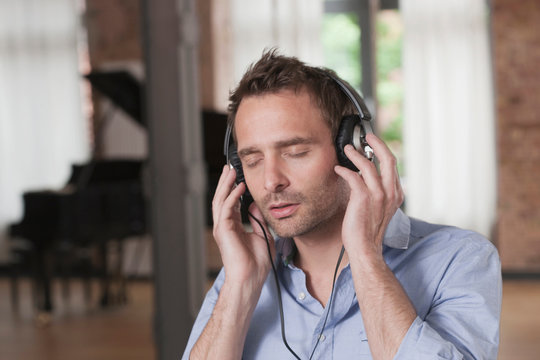 Germany, Man listening music with piano in background