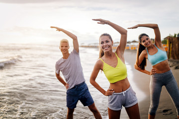 Group of people doing exercises on the beach. Fitness, training, sport and people concept