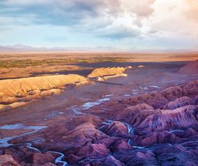 Poster de jardin Grenat Panoramic view of the road leading to Mars Valley near San Pedro de Atacama against a dramatic sunset sky.