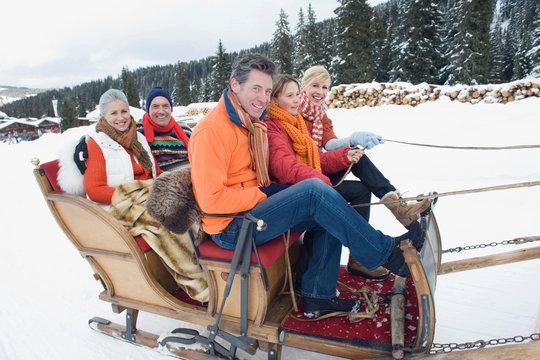 Italy, South Tyrol, Seiseralm, Family riding in sleigh