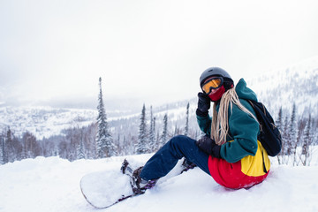 Girl freerider with snowboard in the mountains sitting on a snowy slope..