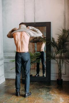 Man putting on cloth at mirror