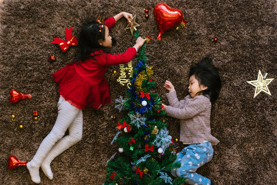 Two adorable girls decorating christmas tree at home