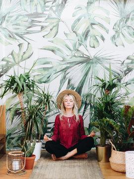 Young woman meditating near plants