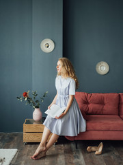 Woman in blue dress on couch