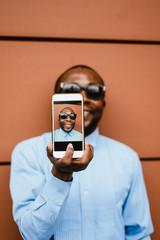 Black man taking selfie on smartphone