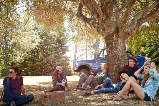 Man relaxing with group of friends in park while on a road trip