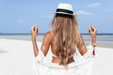 Summer beach tropic island vacations back side portrait of young beautiful tanned woman posing on white sand beach in boho style outfit and having fun alone enjoying the summer