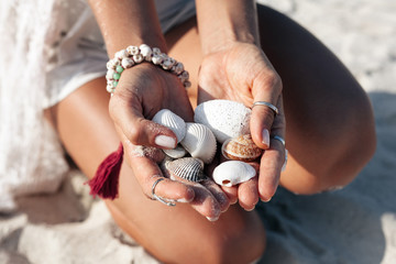 Young beautiful tanned woman are collecting small stones on the beach