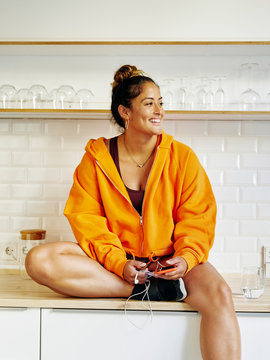 Young woman smiling in the kitchen representing a healthy lifestyle.
