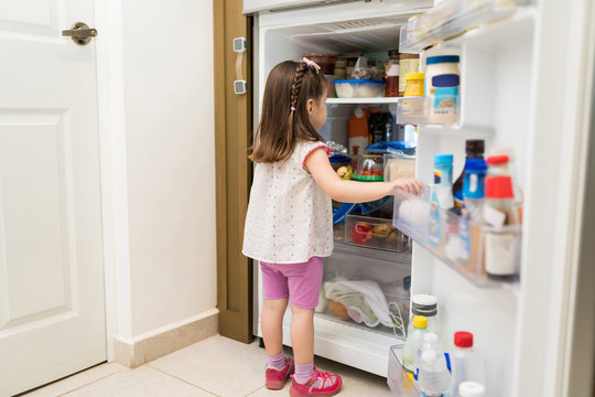 Little Toddler Looking In Refrigerator At Home