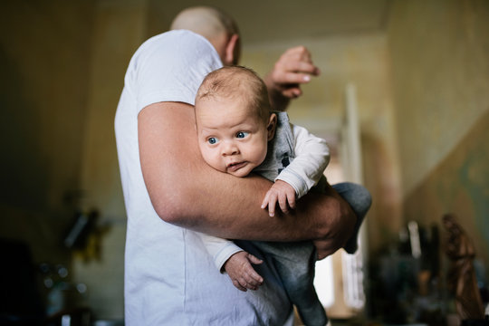 Close-up of newborn in Father's arms
