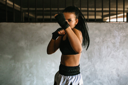 Kickboxing woman training in old gym