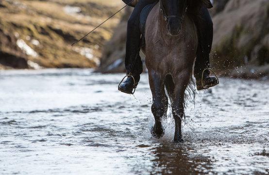 Close-up of a cowboy riding a horse through a river
