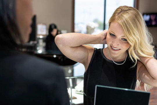 Jewelry: Woman In Luxury Store Trying On A Diamond Necklace