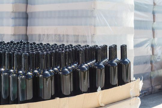 black wine bottles on pallets in outside storage area